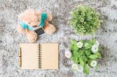 Closeup brown note book diary with blank brown paper space at page with brown pen with artificial plant and bear doll on gray carp. Closeup note book diary with Stock Photos