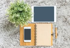 Closeup brown note book , brown pen , computer notebook , tablet , phone and artificial plant on gray fabric capet textured backgr. Closeup note book , brown pen Stock Photos