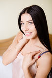 Closeup of brunette girl in camisole smiling on. Closeup portrait of beautiful girl in beige camisole smiling on blurred background. Young lady smiling and stock image