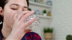 Closeup brunette girl swallows capsule and drinks water. Closeup brunette girl takes and swallows capsule for headache drinking water from glass against kitchen stock video footage