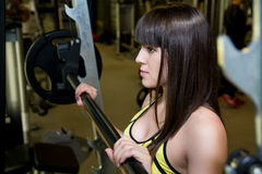 Closeup brunette in the gym. Woman trains his muscles on the sim Stock Photo