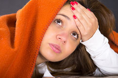 Closeup brunette headshot lying down under orange blanket and blowing her nose, sick with flu concept Royalty Free Stock Photos