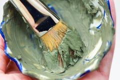 Closeup brush and green clay facial mask in bowl. Skin care. Closeup brush and green clay facial mask in bowl Royalty Free Stock Photos