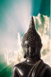 Closeup Buddha statue with dramatic sky background. Stock Photo