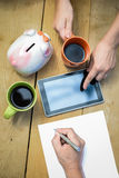 Closeup of budget planning with two cups of coffee. Picture of male hand writing on paper and female hands pointing on tablet. Closeup of family budget or stock images