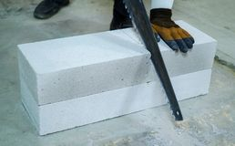 Closeup builder sawing aerated concrete block with hand saw. Male worker in gloves cutting block at construction site. construction, building and manual work stock images