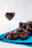 Closeup of a bunch of red grapes and a glass of red wine on back. Ground over a blue tablecloth Stock Photography