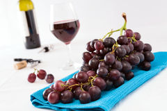 Closeup of a bunch of red grapes and a glass of red wine with a. Wine bottle on background over a blue tablecloth Royalty Free Stock Images