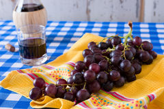 Closeup of a bunch of red grapes and a glass of red wine. On a checkered tablecloth Stock Images