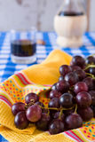 Closeup of a bunch of red grapes and a glass of red wine with a. Wine flask on background over a checkered tablecloth Stock Image