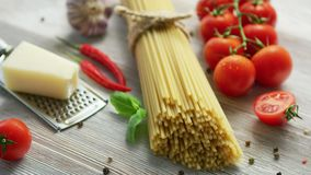 Ingredients for cooking pasta. Closeup of bunch of tied spaghetti on wooden table with ripe tomatoes and piece of cheese with condiments around stock footage