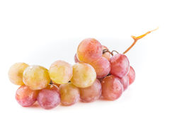 Closeup of a bunch of yellow and red grapes. On the vine laying on a white background Stock Image