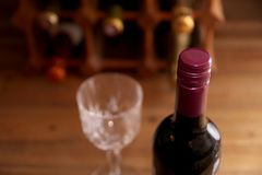 Closeup of burgundy screw top wine bottle with wine rack and win. E glass in out of focus background Stock Images