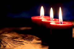 Closeup of burning candles on black background, christmas, holid Stock Photos