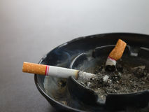 Closeup burning cigarette in ashtray and smoke Stock Photo