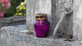 Closeup of burning purple candle and small crucified jesus figure. 4K