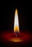 Closeup of a burning red candle Stock Photos