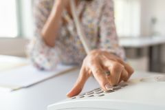 Closeup of business assistant pressing a button on telephone keypad stock image