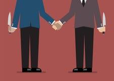 Closeup of business handshake with a knife hidden behind Stock Photos