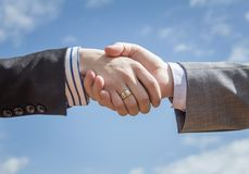 Closeup of business handshake over sky background Royalty Free Stock Image