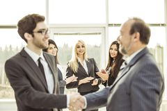 Handshake business partners before beginning business negotiations on the background of applauding. Closeup of a business handshake partners before beginning Stock Image