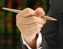Closeup business man. Hold a pen and stock exchange board background royalty free stock photography