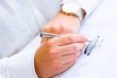 Closeup of a business man analysing graph. Closeup of a business man holding a pen in hand analysing pie chart and making notes Stock Photography