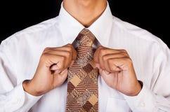 Closeup of business man fixing his neck tie Royalty Free Stock Photos