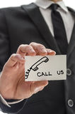 Closeup of a business man handing card with Call us message. Closeup of a business man handing  card with Call us message written on it Stock Images