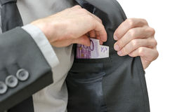 Putting banknotes in a jacket pocket Stock Photo