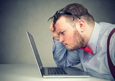 Business man taking off his glasses having eyesight problems confused with laptop royalty free stock photography