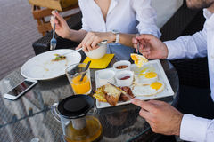 Closeup of business people hands, male and female having breakfast at outdoors cafe. Meals with salad, omelette, bacon. Stock Photo