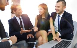 Closeup.business team holds a discussion. Sitting near the table Stock Image