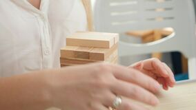 Closeup of business woman building tower from wooden blocks and bricks. Concept of stability, development, success and