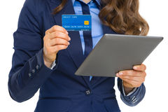Closeup on business woman with credit card using tablet pc Stock Image