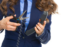 Closeup on business woman cutting phone wire Royalty Free Stock Image