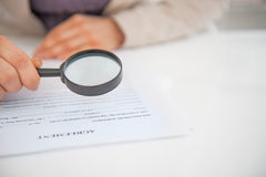 Closeup on business woman exploring document. With magnifying lens Royalty Free Stock Image