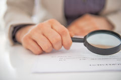 Closeup on business woman exploring document. With magnifying lens Royalty Free Stock Images