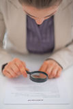 Closeup on business woman exploring document. With magnifying lens Stock Image