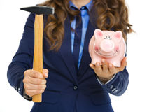 Closeup on business woman giving piggy bank and hammer Royalty Free Stock Photography