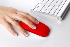 Closeup of business woman hand using wireless computer mouse and keyboard. Royalty Free Stock Photography