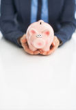 Closeup on business woman holding piggy bank Stock Images