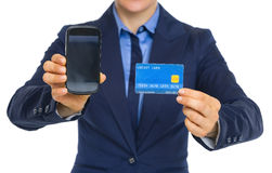 Closeup on business woman showing phone and credit card Stock Photos