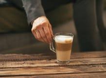 Closeup on business woman taking coffee latte Stock Photos