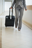 Closeup on business woman walking with wheel bag Royalty Free Stock Image