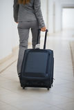 Closeup on business woman walking with wheel bag Royalty Free Stock Images