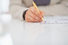 Closeup on business woman writing in document Stock Images