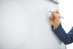 Closeup on business woman writing on flipchart Royalty Free Stock Photos