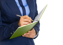 Closeup on business woman writing in notepad Stock Image
