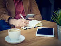 Closeup of businessman in cafe shop using his phone and notebook Royalty Free Stock Images
